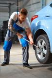 Car Mechanic Changing Tire in Professional Car Repair Service