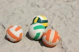 Fototapeta Vier Bälle für Volleyball auf einem Sandplatz