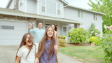 A family runs out of their house towards the camera and then stops and smiles