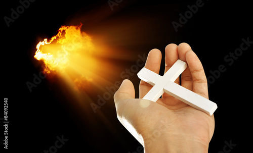 Hand and cross on light beams background