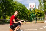 Fototapeta Athletic Woman Sitting on Basketball on Court