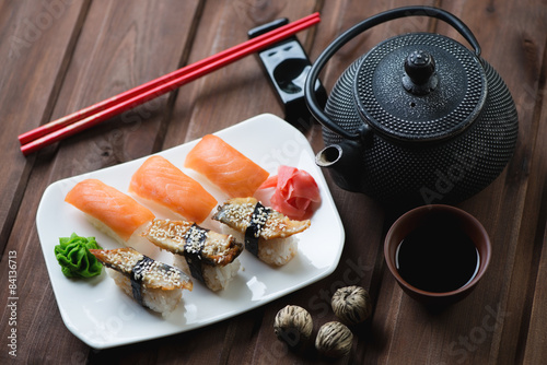 Fototapeta Sushi set with chopsticks and tea over dark wooden background