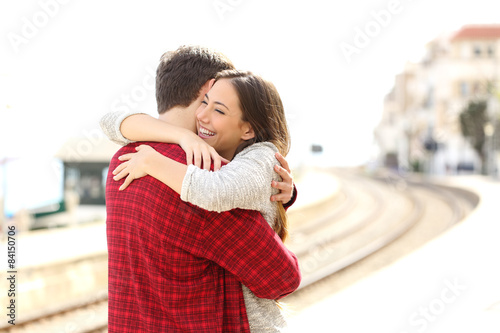 Poster Couple hugging happy in a train station