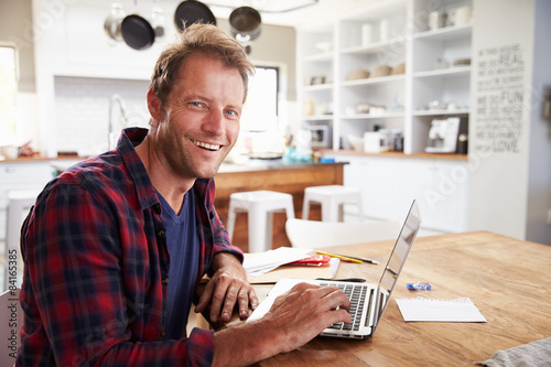 Man working on laptop at home Poster