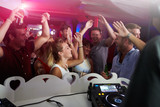 People Dancing In Nightclub With DJ In Foreground