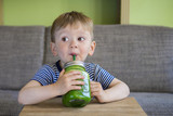 Fototapety Little boy drinking a green smoothie
