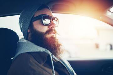 bearded hipster wearing sunglasses inside car