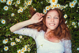 Fototapety Beautiful young girl with curly red hair in camomile field