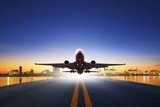 Fototapeta cargo plane take off from airport runways against ship port back