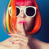 Fototapety beautiful woman wearing colorful wig and white sunglasses agains