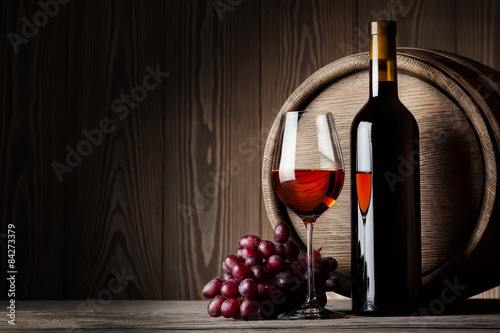 Black bottle and glass of red wine with grapes and barrel Poster