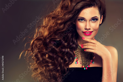 Fototapeta Beautiful model brunette with long curled hair.