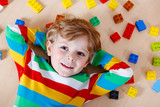 Fototapety Little blond child playing with lots of colorful plastic blocks