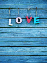 The word Love with wooden multi colored letters on natural board