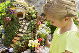 Child looking at fairy garden in a flower pot outdoors