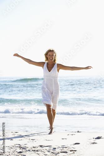 Young Woman Running Along Beach - 84417378