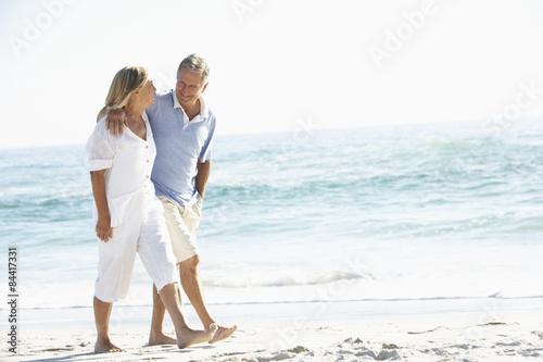 Senior Couple On Holiday Walking Along Sandy Beach Poster