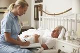 Fototapety Nurse Visiting Senior Male Patient In Bed At Home