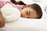 Young Girl Asleep In Bed With Cuddly Toy poster
