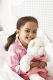 Young Girl Wearing Pajamas In Bed With Cuddly Toy poster