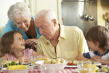 Fototapety Grandparents And Grandchildren Eating Meal Together In Kitchen