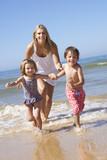 Mother Chasing Children Along Beach