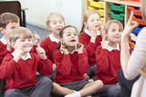 Fototapety Pupils Copying Teacher's Actions Whilst Singing Song