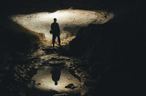 Fototapety man silhouette reflecting in water in dark cave