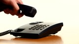 Businessman making a phone call on landline telephone