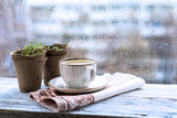 Cup with warm drink on wooden table in front of window with rain drops, rainy weather. Moody still life. Cold pale tones, horizontal image