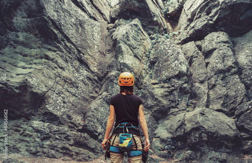 Climber woman standing in front of a stone rock outdoor