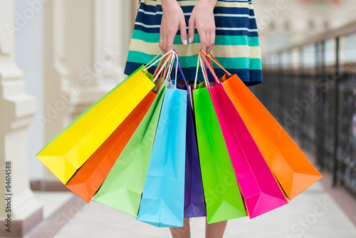 Poster Woman holding colourful shopping bags at the mall.