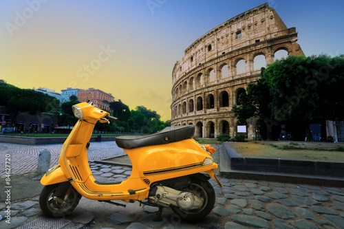 Poszter Yellow vintage scooter on the background of Coliseum