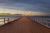 drewniane molo przez morze oświetlone przez stylowe lampy w nocy