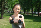 Fitness woman mimics a hit with light dumbbells poster