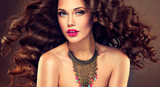 Fototapety Beautiful model brunette with long curled hair and jewelry necklace