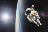 Fototapeta Astronaut in outer space with planet earth as backdrop. Elements
