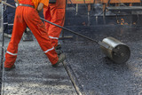 Worker pushing hand roller for mastic asphalt paving poster