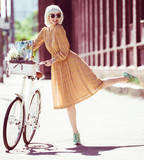 Hipster painter. Fashion blond woman with retro white bicycle