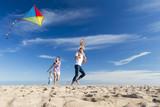 Fototapety Family on the Beach Flying a Kite