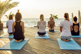 group of young females practicing yoga on the seaside during the sunrisе