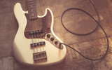 Fototapety old vintage electric bass guitar on basement floor