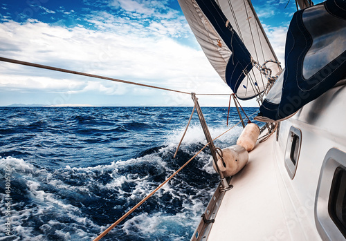 Fotobehang Zeilen The white sails of yachts on the background of sea and sky in the clouds