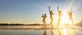 Glückliche junge Menschen laufen und springen am See beim Sonnenuntergang - Fine Art prints