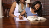 Portrait of African American mother helping her daughter with homework