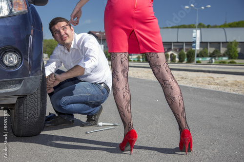 poster of Dominatrix female directs man to repair car. Leggy female body sexy stockings pointing her hand towards car wheel to be fixed by conformable man roadside outdoor sunny day blue sky