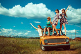 Four beautiful woman are dancing on the old car. Green fields on - Fine Art prints