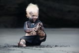 Funny portrait of smiling child with dirty face sitting and playing with fun on black sand sea beach before swimming in ocean. Family active lifestyle, and water leisure on summer vacation with baby - Fine Art prints