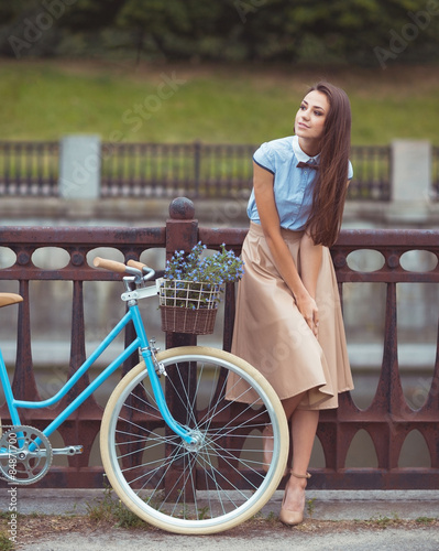 Young beautiful, elegantly dressed woman with bicycle. Beauty, f