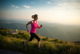 Fototapeta beautiful young woman runns cross country on a mountian path at